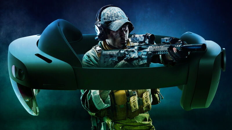A soldier raises a rifle from within a comically oversized headset.