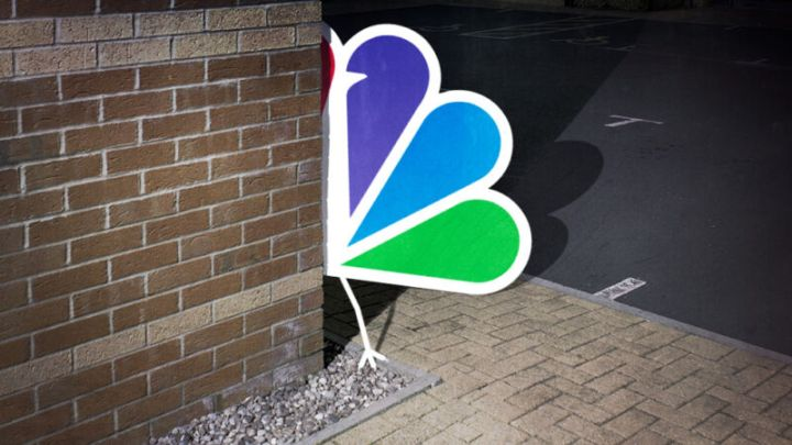An NBC peacock logo is on the loose and hiding behind the corner of a brick building.