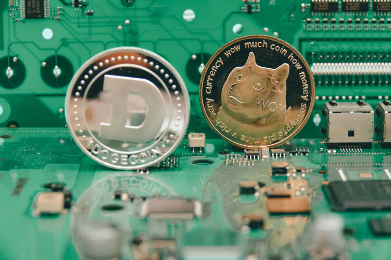 Physical representations of virtual dogecoins sit atop computer components.