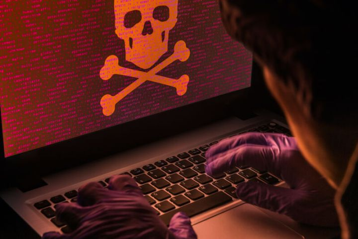Gloved hands manipulate a laptop with a skull and crossbones on the display.
