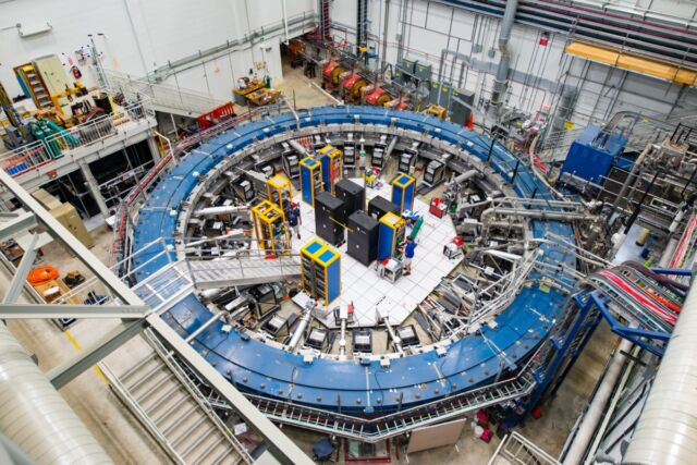 The Muon g-2 ring sits in its detector hall amid electronics racks, the muon beamline, and other equipment. This experiment studies the precession (or wobble) of muons as they travel through the magnetic field.