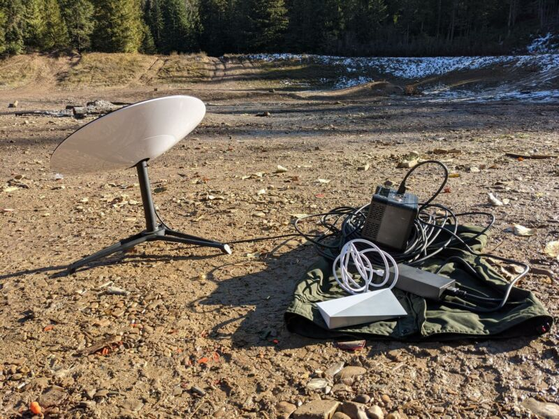 A Starlink satellite dish sits on the ground in a clearing in the middle of a forest.