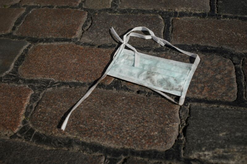 A thrown-away surgical mask lays on the ground.