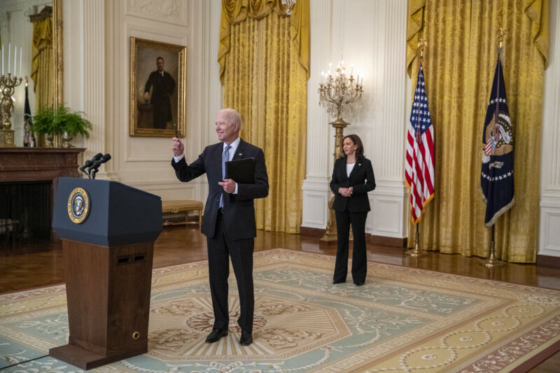 An older man in a suit speaks casually from behind a podium.