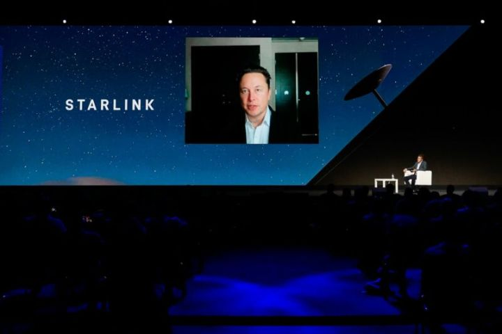 SpaceX CEO Elon Musk appears on a giant video screen while he discusses Starlink.