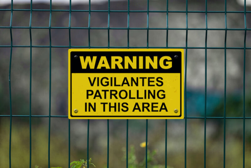 A warning sign on a grid-style metal fence.