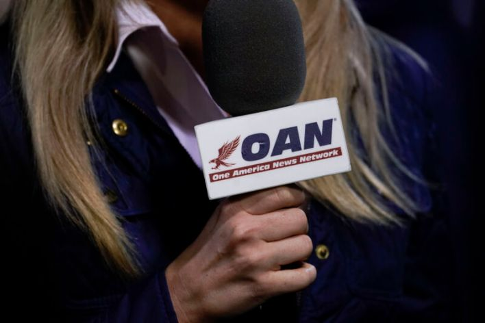 OAN-branded microphone in the hand of a longhaired reporter.