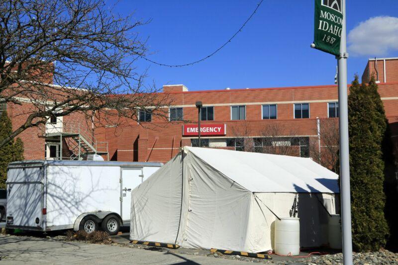 Large tents set up outside a brick building.