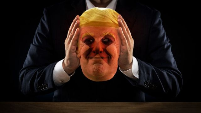 A shadowy figure holds a mask of Donald Trump.