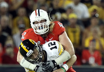 TUCSON, AZ - SEPTEMBER 18:  Quarterback Ricky Stanzi #12 of the Iowa Hawkeyes is sacked by Brooks Reed #42 of the Arizona Wildcats during the third quarter of the college football game at Arizona Stadium on September 18, 2010 in Tucson, Arizona.  The Wildcats defeated the Hawkeyes 34-27.  (Photo by Christian Petersen/Getty Images)