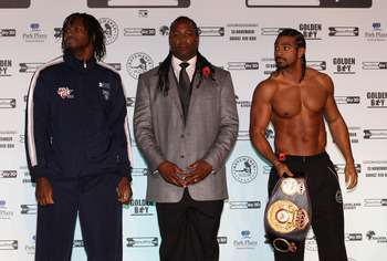 MANCHESTER, ENGLAND - NOVEMBER 12:  Former heavyweight champion of the world, Lennox Lewis, steps in between David Haye and Audley Harrison as they go face to face during the official weigh-in at The Lowry Theatre on November 12, 2010 in Manchester, Engla