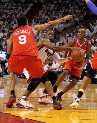 MIAMI, FL - APRIL 18:  Dwyane Wade #3 of the Miami Heat passes around Andre Iguodala #9 of the Philadelphia 76ers during game two of the Eastern Conference Quarterfinals at American Airlines Arena on April 18, 2011 in Miami, Florida. NOTE TO USER: User ex