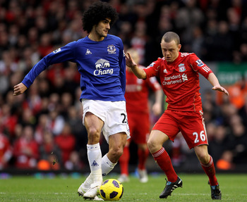LIVERPOOL, ENGLAND - JANUARY 16:  Marouane Fellaini of Everton is challenged by Jay Spearing of Liverpool during the Barclays Premier League match between Liverpool and Everton at Anfield on January 16, 2011 in Liverpool, England. (Photo by Alex Livesey /