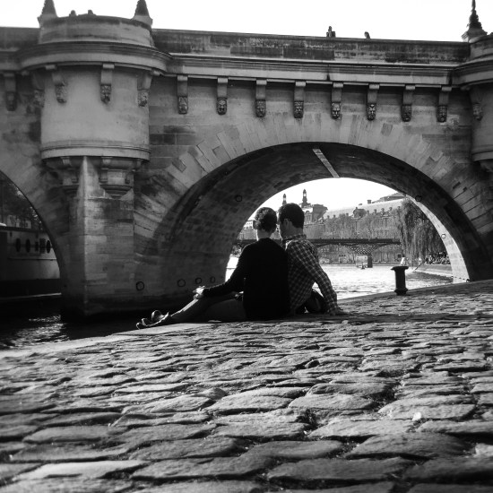 A couple sits along the edge of the Seine River in Paris, France.