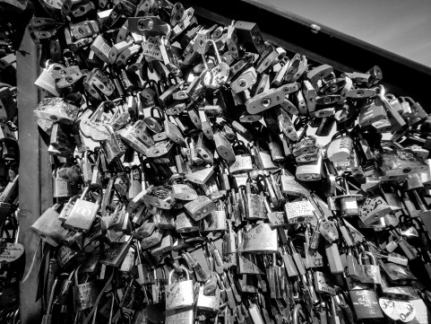 Love lock line the hand rail of a bridge in Paris, France. The city has begun to remove the locks by replacing the iron railings.
