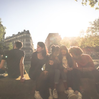 Friends huddle to watch a video on a cell phone in Paris, France.