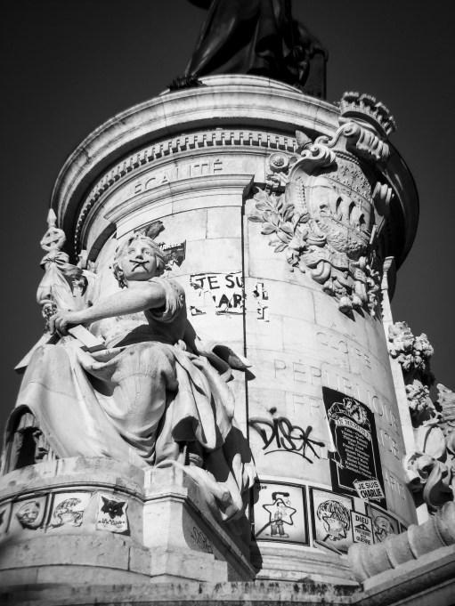 Monument covered in graffiti at Place de la République in Paris, France.