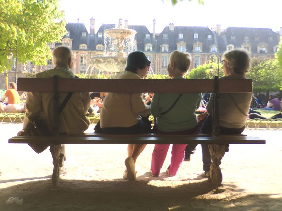 Three women meet to talk on a park bench in Paris, France.