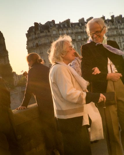 Two old friends stop along the bank of the Seine River in Paris, France to enjoy the golden light.