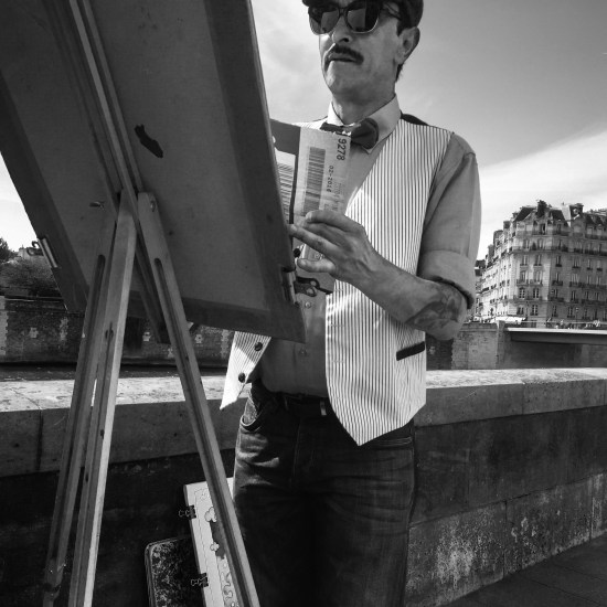 A painter sketches a scene along the banks of the Seine River in Paris, France.