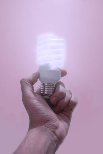 person holding a turned on light bulb