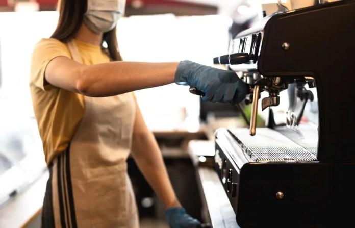 Una mujer prepara un café en un bar.