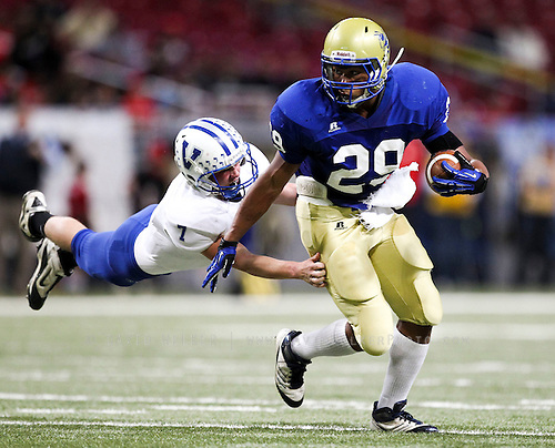 Kellen Overstreet (29) of the Penny Hornets breaks away from Nolan Wood (7) of the Valle Catholic Warriors during the 2012 MSHSAA football class 1 state championship game at the Edward Jones Dome on November 23, 2012 in St. Louis, Missouri.