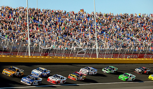 Photo of NASCAR fans in packed stands with NASCAR stock cars on the track.