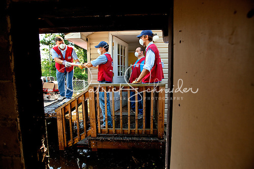 Photography of employee volunteers helping a flood victim move possessions from a flooded house in Florida.