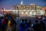 The Diamond Princess lit up at night while media looks through a chain link fence
