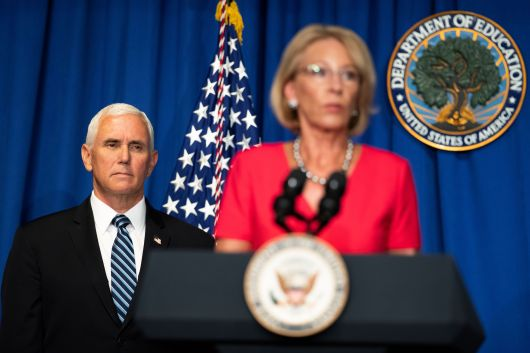 Vice President Mike Pence listens to Education Secretary Betsy DeVos speak during a White House Coronavirus Task Force briefing at the Department of Education building, in Washington on July 8th.