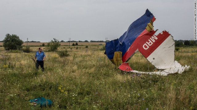 A Ukrainian police officer searches for human remains at the crash site in July 2014.