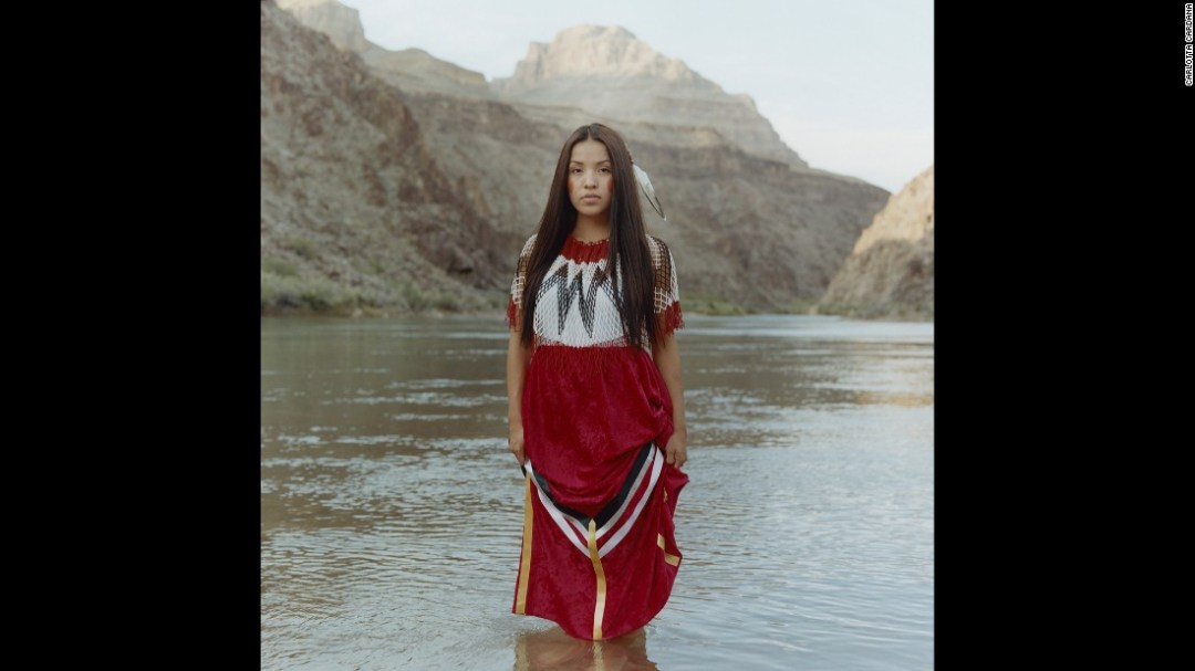 """Sage Honda, a 22-year-old from Peach Springs, Arizona, wears a handmade dress at the Grand Canyon, a sacred site of the Hualapai people. Since appearing in Miss Native American USA, she has been encouraging Native youth to travel off the reservation to explore more opportunities. """"I want to be a role model to show my community and youth that it is possible to come off our land and do big things,"""" she said in the """"Red Road"""" photo series."""