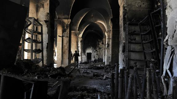 A Syrian rebel walks inside a burnt section of the Umayyad Mosque in Aleppo hours before the Syrian army retook control of the complex on October 14, 2012.