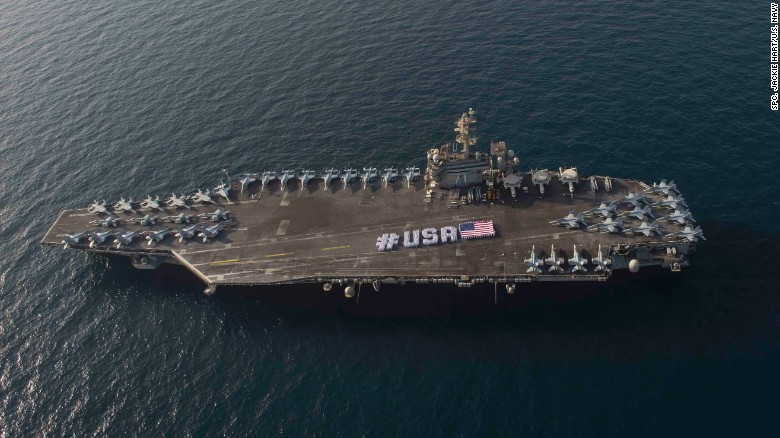 Sailors spell out #USA with the American flag on the flight deck of the Nimitz-class aircraft carrier USS Theodore Roosevelt in the Persian Gulf in late June 2015. When the Roosevelt leaves the Gulf sometime in October, the U.S. Navy will be without a carrier in the important region for two months.
