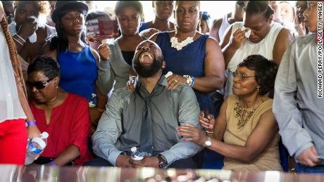 Michael Brown Sr. cries out as the casket is lowered into the ground during the funeral of his son.