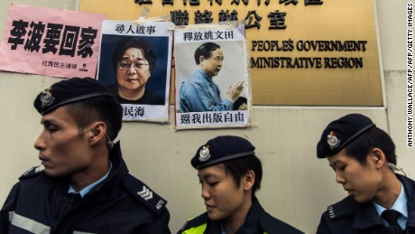 Police walk past a missing person notice of Gui Minhai (L), one of five booksellers from Hong Kong's Mighty Current publishing house who went missing in 2015.