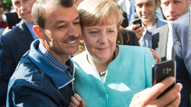 Image result for merkel with refugees, photos