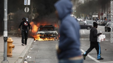 People walk past burning cars near the intersection of Pennsylvania Avenue and North Avenue in Baltimore on April 27, 2015. Riots erupted in the city following the funeral service for Freddie Gray, who died while in Baltimore Police custody.