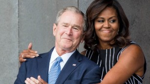 Former US President George W. Bush receives a hug from US First Lady Michelle Obama on September 24, 2016 in Washington, D.C.