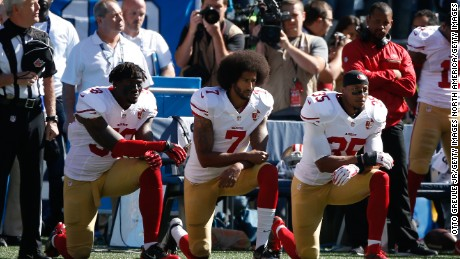 Colin Kaepernick #7 and members of the San Francisco 49ers kneel during the national anthem prior to the game against the Seattle Seahawks on September 25, 2016 in Seattle, Washington.