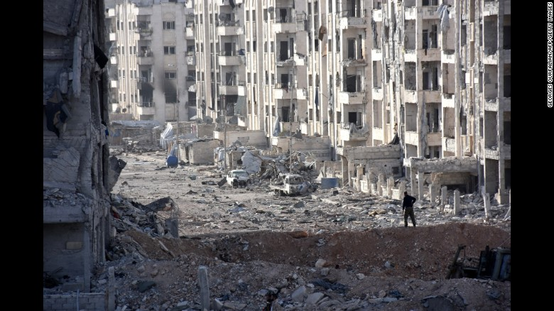 A member of the Syrian pro-government forces stands amid heavily damaged buildings in Aleppo's 1070 district on November 8, 2016, after troops seized it from rebel fighters.