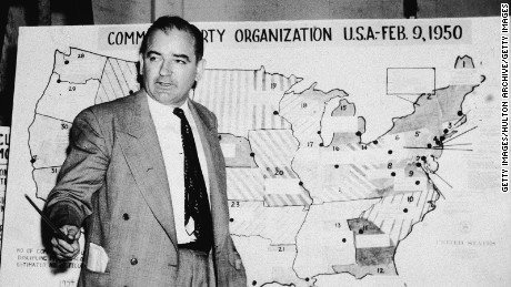 Joseph McCarthy, a Republican senator from Wisconsin, stands before a map which charts Communist activity in the United States in 1954.