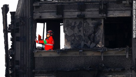 Emergency services crews work on the top floor of the charred remains of the Grenfell Tower.