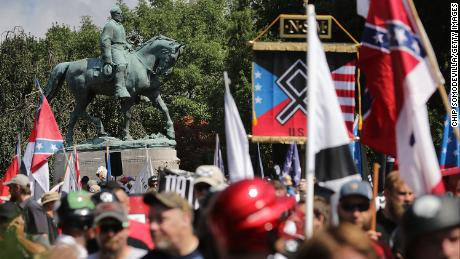 The statue of Confederate General Robert E. Lee stands behind a crowd of hundreds of white nationalists, neo-Nazis, and members of the