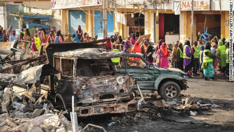 People gather near burned vehicles a day after a truck bomb exploded in the center of Mogadishu on October 15.