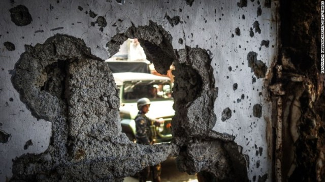 A Philippine soldier is seen past a hole in the wall of a damaged building in the Mapandi area of Marawi on the southern island of Mindanao on August 30, 2017.