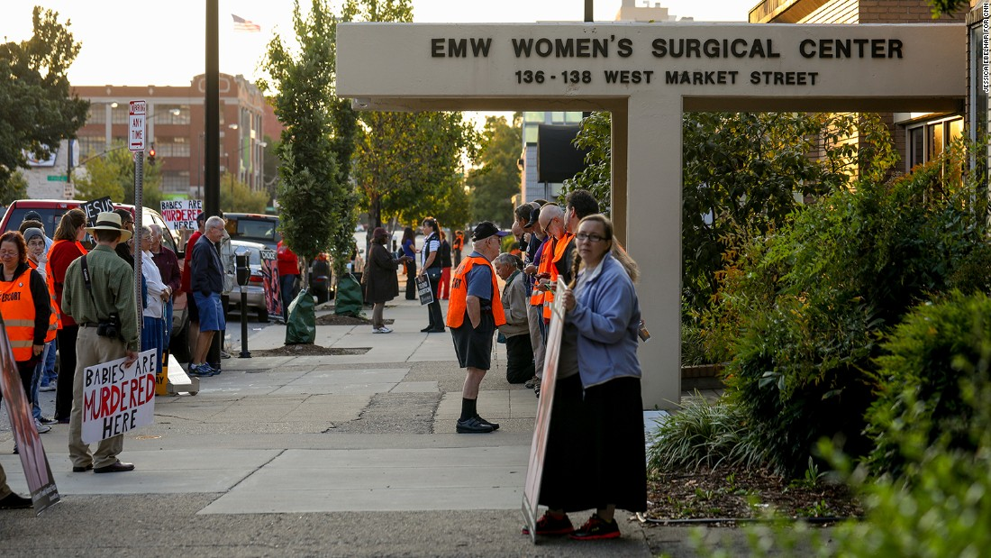 Anti-abortion demonstrators and volunteer clinic escorts are seen outside the EMW Women's Surgical Center in Louisville, Ky. on Aug. 26, 2017. The volunteer escorts wear vests to identify themselves.