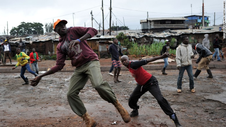 Residents throw stones towards Kenyan police officials as they clash at Katwekera village within Kibera slum - a stronghold of opposition leader Raila Odinga on Thursday.