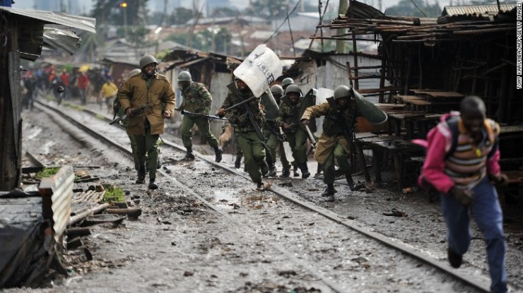 Kenyan officers charge at stone-throwing residents during clashes in Kibera on Thursday